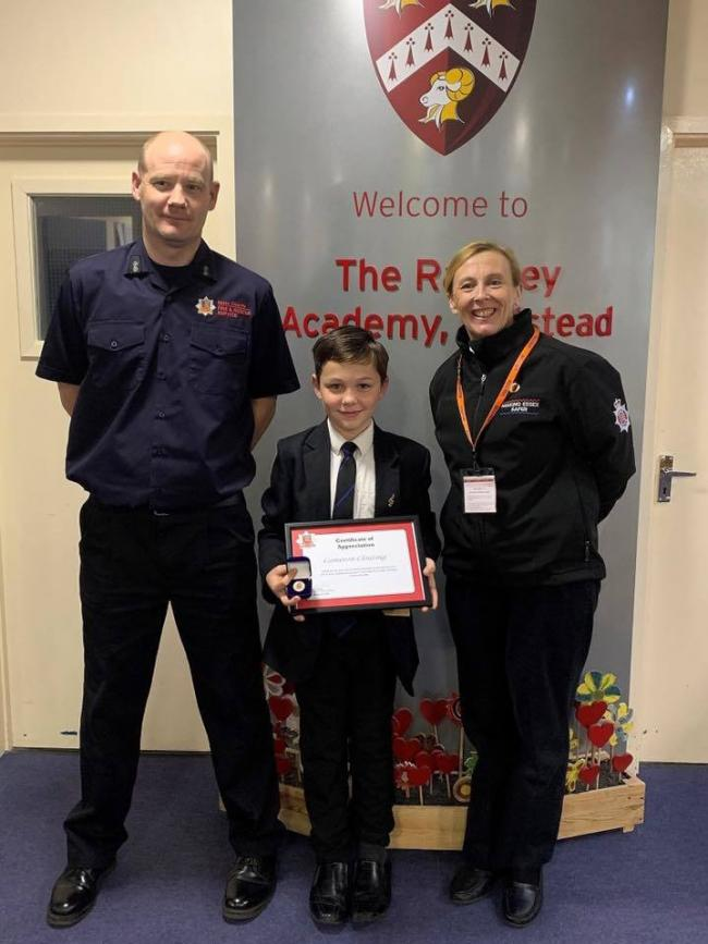 (CREDIT: Essex County Fire and Rescue Service) Cameron (centre) received a certificate of recognition and a service badge from Steve Byrne (left) and Andrea Adams (right)