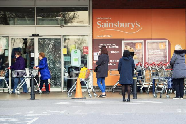 Shoppers queue outside a Sainsbury's supermarket