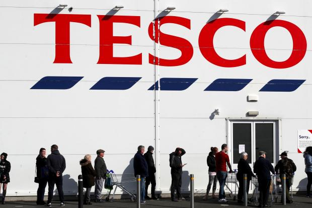 Gazette: People queue outside a Tesco Extra store in Madeley, Shropshire
