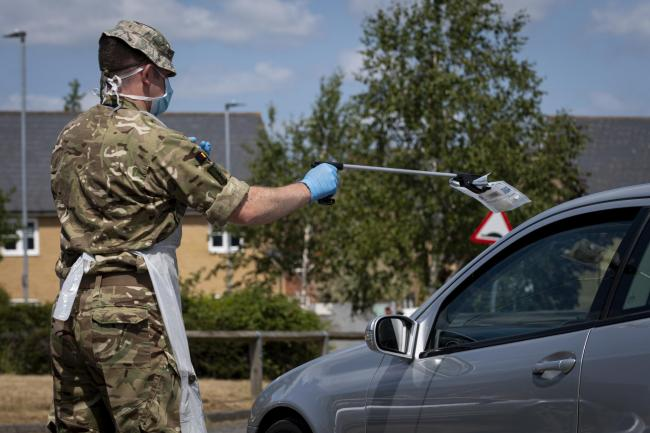 .A soldier from 3rd Battalion The Royal Anglian Regiment.Essex Reservists carries covid testing packs to be placed in a refrigeration unit prior to be sent off for testing...Essex Reservists working on the county's coronavirus frontline..Army Reserve