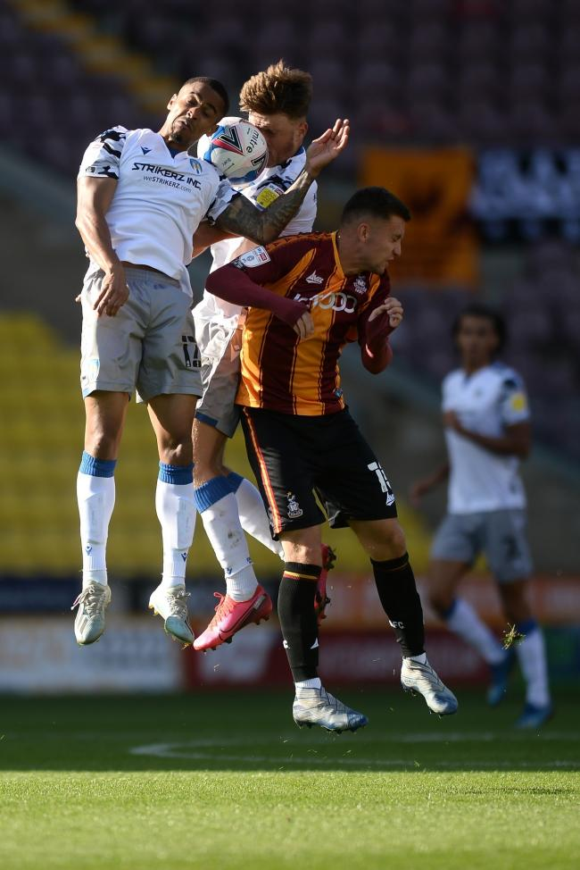 Heads up - Colchester United duo Paris Cowan-Hall and Noah Chilvers in action against Bradford City's Elliot Watt Picture: RICHARD BLAXALL
