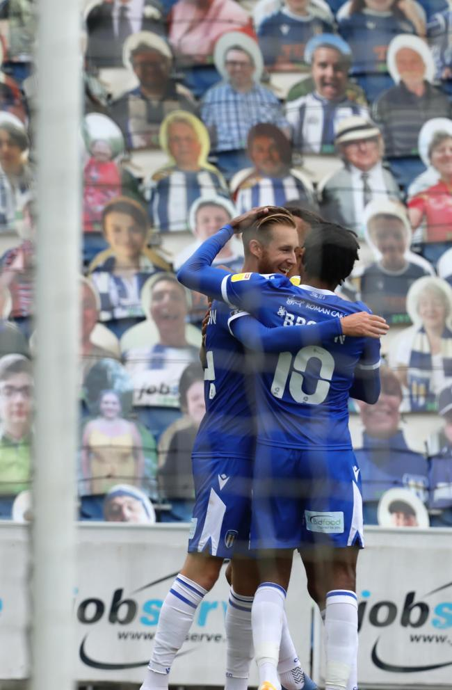 Watching on - Ben Stevenson and Jevani Brown celebrate a U's goal at the JobServe Community Stadium with Colchester United fans cut-outs in the background Picture: STEVE BRADING