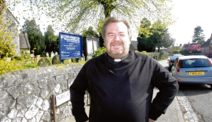 Parking problem – the Rev Raymond Gibbs outside St Michael's Church, with cars lined up down the road