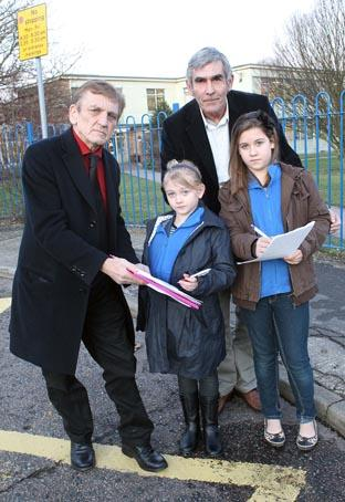 Tiana Page, eight, and sister Brooke, ten, sign the petition with councillors Dave Harris and Kim Naish at Monkwick Junior School
