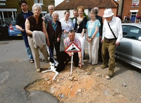 Sort it out – Robert Needham holds a warning sign at a pothole in Wivenhoe with mayor Penny Kraft, deputy mayor Andrea Vaughn and concerned residents