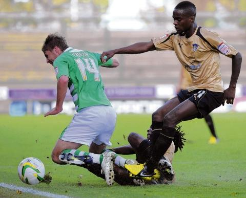 Setback - Gavin Massey (right) battles it out with Sam Foley on his return to Huish Park. Picture: WARREN PAGE