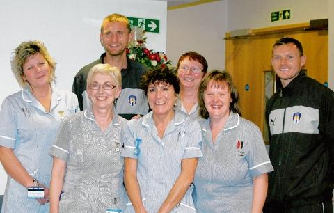 Col U players Matt Heath (left) and Brian Wilson visit St Helena Hospice nurses (from left) Sue Lucas, Liz Mills, Sharon Harris and at the back Christine Newman