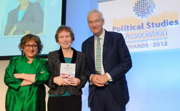 Professor Vicky Randall receives her award from Jon Snow and a member of the Political Studies Association.