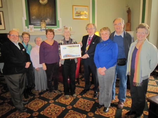 Colchester Mayor Christopher Arnold is presented with a certificate by members of the Colchester Fairtrade Town Group.