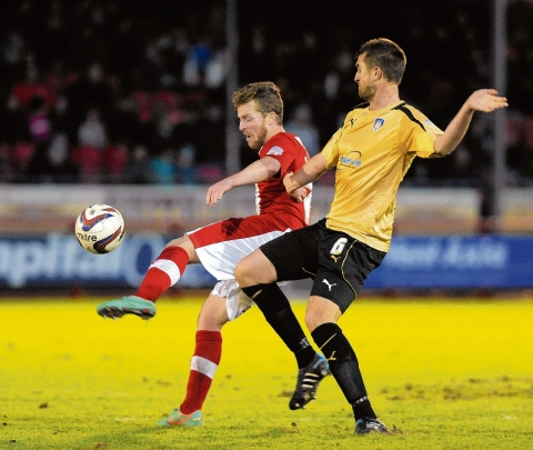 Eye on the ball - Colchester United defender Matt Heath does battle with Crawley's Billy Clarke during the U's 3-0 defeat at the Broadfield Stadium. Picture: WARREN PAGE