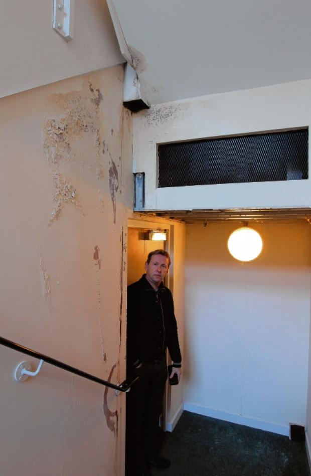 Tony Benfield in the communal hallway leading to his penthouse flat