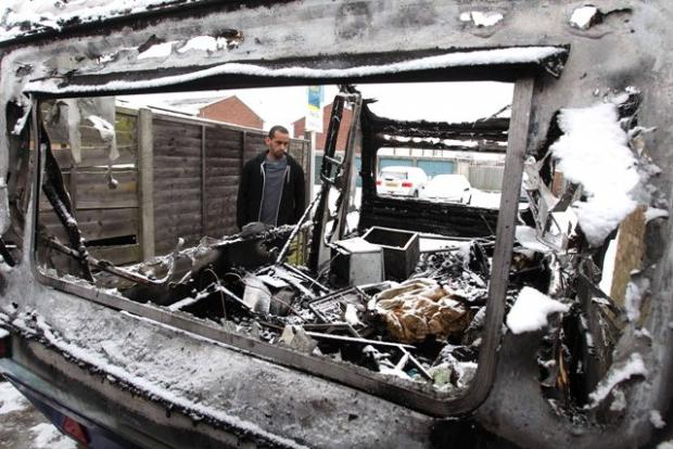 Raymond Griffiths, son of the caravan's owner Roy, surveys the burnt out shell of the caravan.