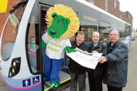 Dandylion from St Helena Hospice accepts the cheque from bus drivers John Smith, Dilwyn Faircloth and Kevin Howard.