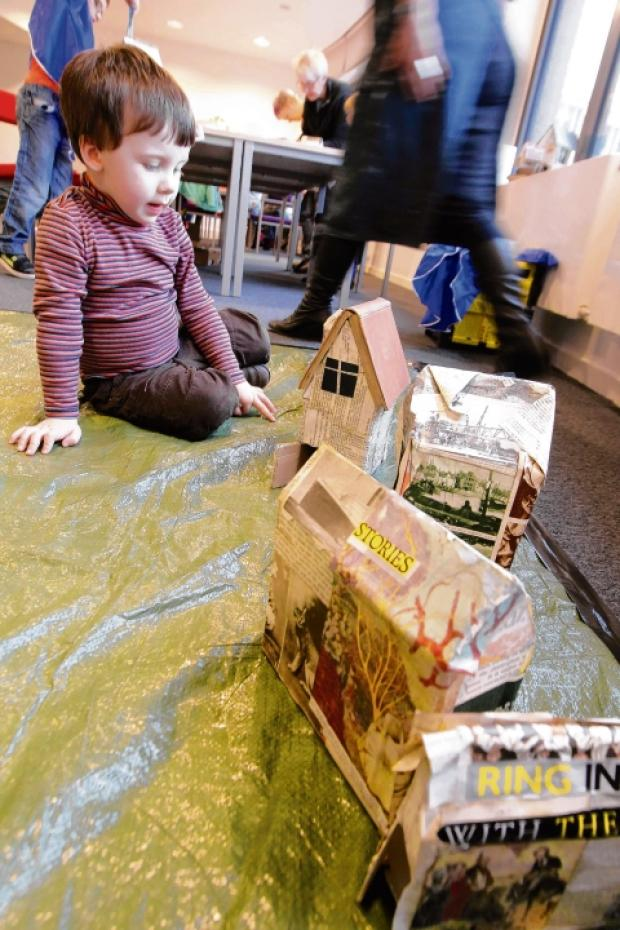 James Darroch, three, placing a book roof on a model house.