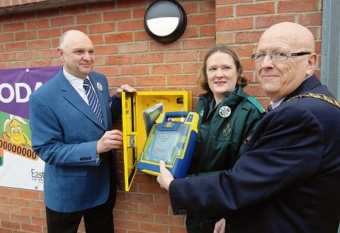 New defibrillator fitted to the wall of Mersea Co-op from left, Co-op director Colin Barrett, Lorna Hayes from the East of England Ambulance Service and town mayor John May.