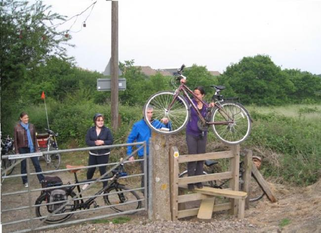 Cyclists work together as they struggle to cross the railway line on the path linking Essex University with the Wivenhoe Trail.