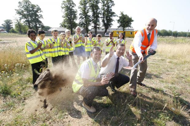 St John's Green pupils watch (from left) county councillor Don Parker, headteacher  Simon Billings and county councillor Ray Gooding cutting the first sod.