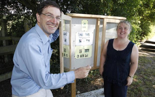 Paul Smith and Paula Baker unveil new notice board in St John's.