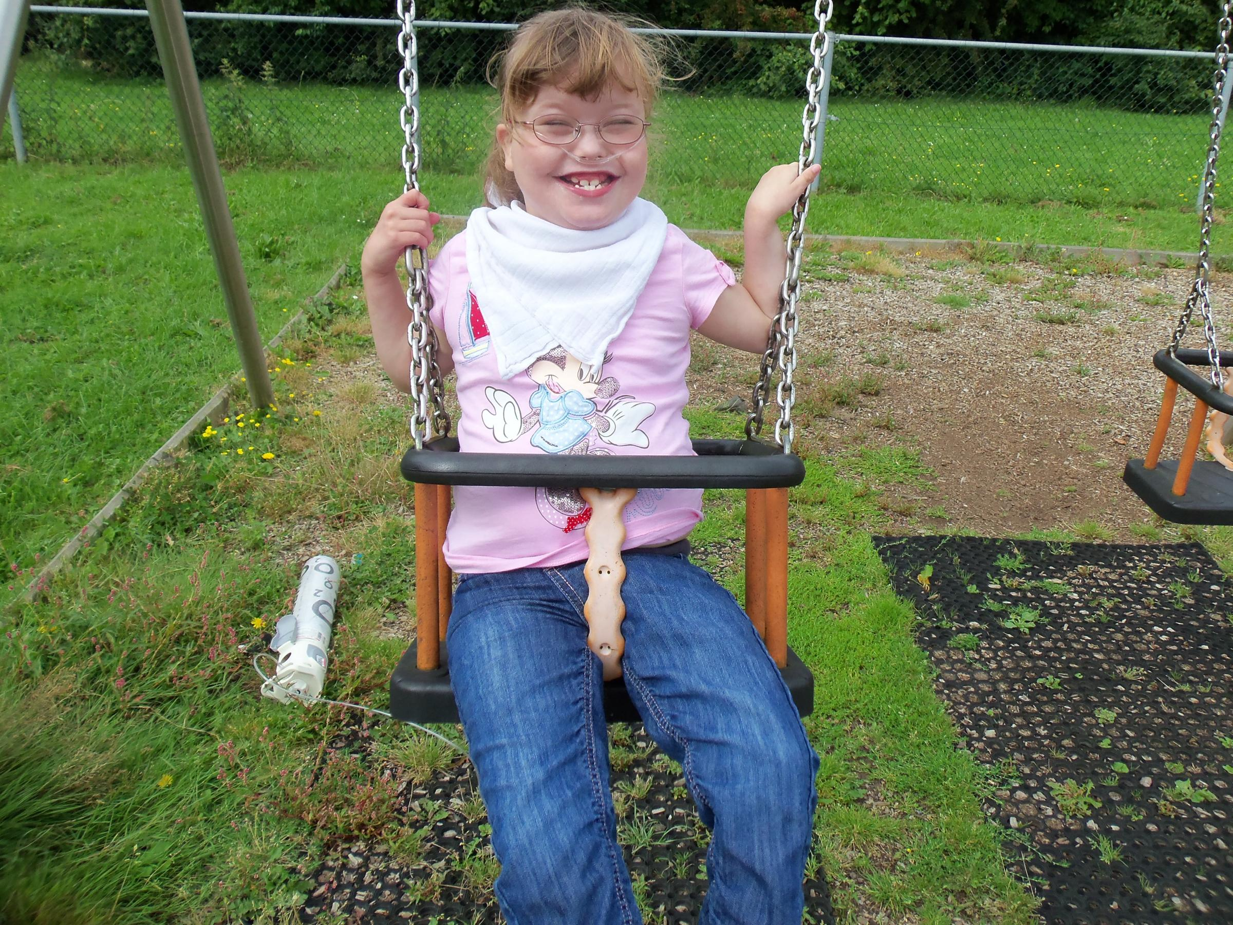 Jess enjoys playing on a special swing