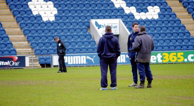 Disappointment - U's groundsman David Blacknall chats to U's assistant manager Mark Kinsella and Shrewsbury caretaker boss Mike Jackson, as referee Gary Sutton assesses the pitch. Picture: ADRIAN RUSHTON (CO90149-09)