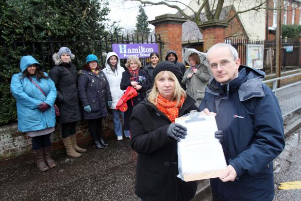 Gazette: Parent Sam Hempstead with headteacher Clive Reynolds and other parents concerned about the council's parking proposals.