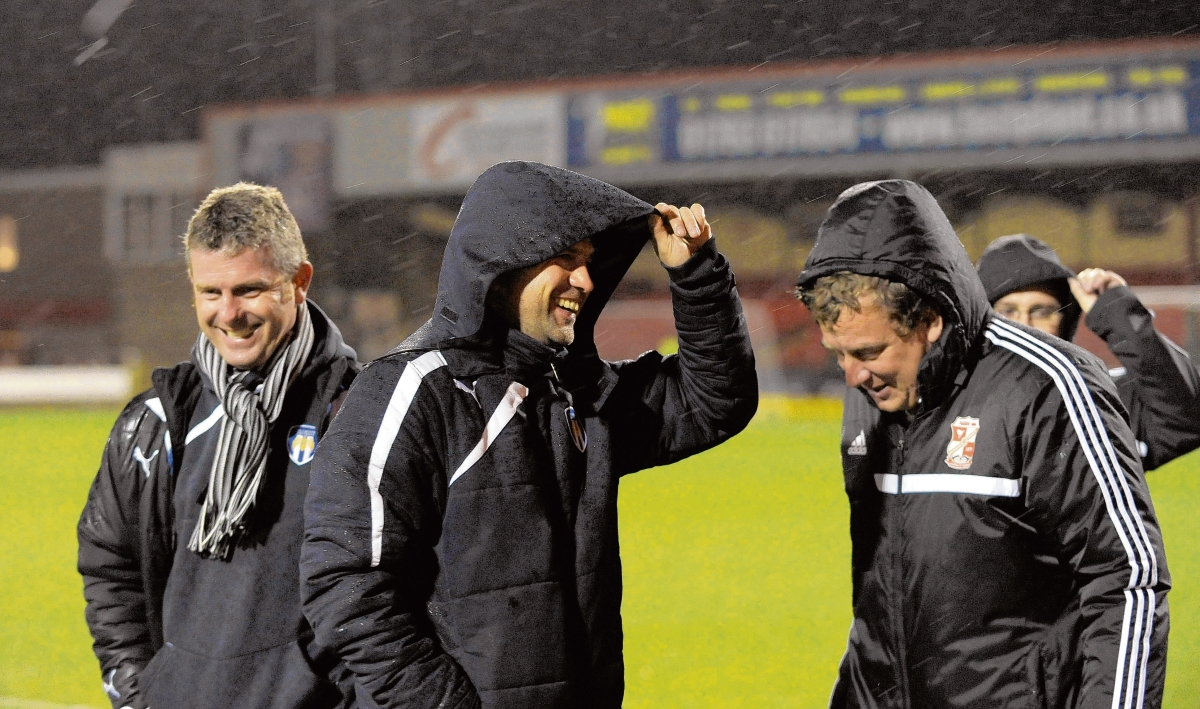 Laughing in the rain - Colchester United manager Joe Dunne (centre) and assistant manager Mark Kinsella (left) share a joke with a Swindon Town staff member prior to the sides' 0-0 draw at a stormy County Ground, last Friday. Picture: WARREN PAGE