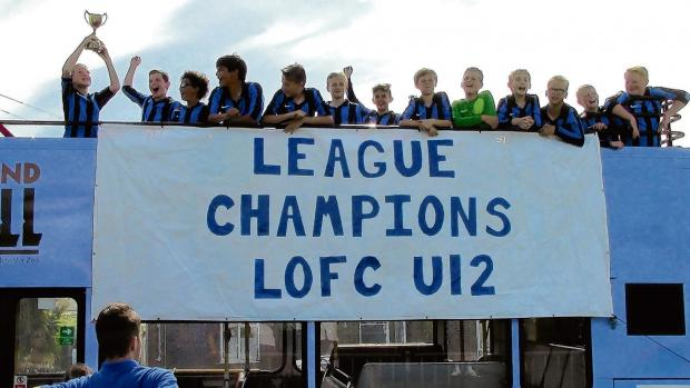 Youth footballers celebrate their title success in style - with an open-top bus parade