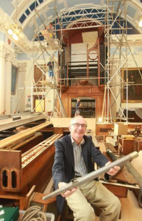 Nigel Chapman with one of the pipes from the Moot Hall organ