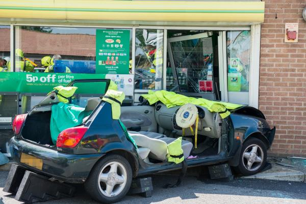 Pair trapped after car crashes into petrol station shop on the A12