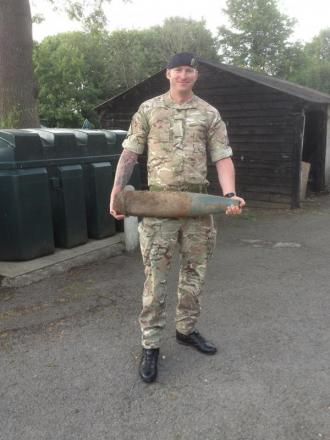 A member of the army's bomb squad with the shell