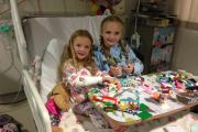 Chloe (right) visited by her sister Ellie in hospital