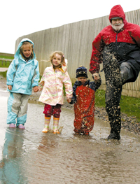 Making the most of the puddles - councillor Michael Talbot with his grandchildren, Sophie, 4, Molly, 4, and Lotti, 2. Picture: STEVE BRADING (53455-e)