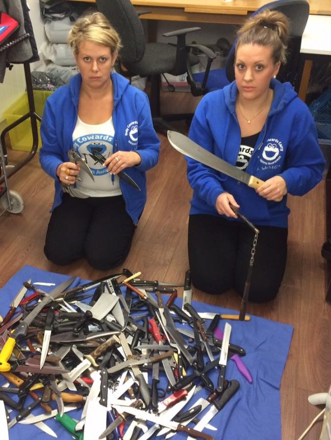 Sarah Cordrey and Charmaine Wilson, of the Only Cowards Carry charity, display the knives collected in Clacton