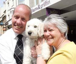 Ajay the labradoodle, who is being trained as a guide dog, with namesake Andrew J Faint and Teresa Marshall.