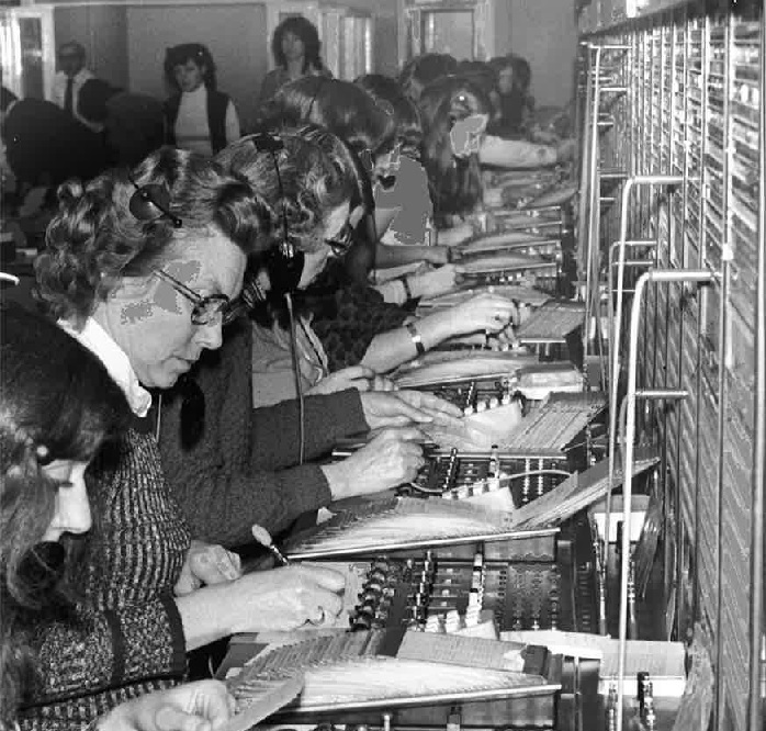Staff working in the telephone exchange in 1979 when they still had to look everything up.