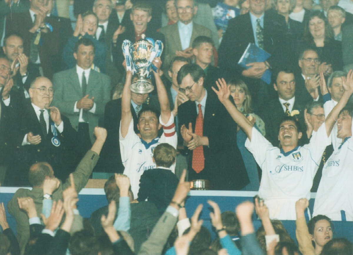 Glory - Colchester United skipper Richard Wilkins lifts the division three play-off trophy at Wembley, in 1998