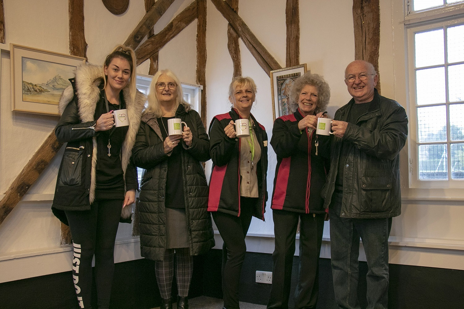 Thanks - staff from the East of England Co-op handover mugs to groups who have left Duchy Barn, Dedham, while they moved in