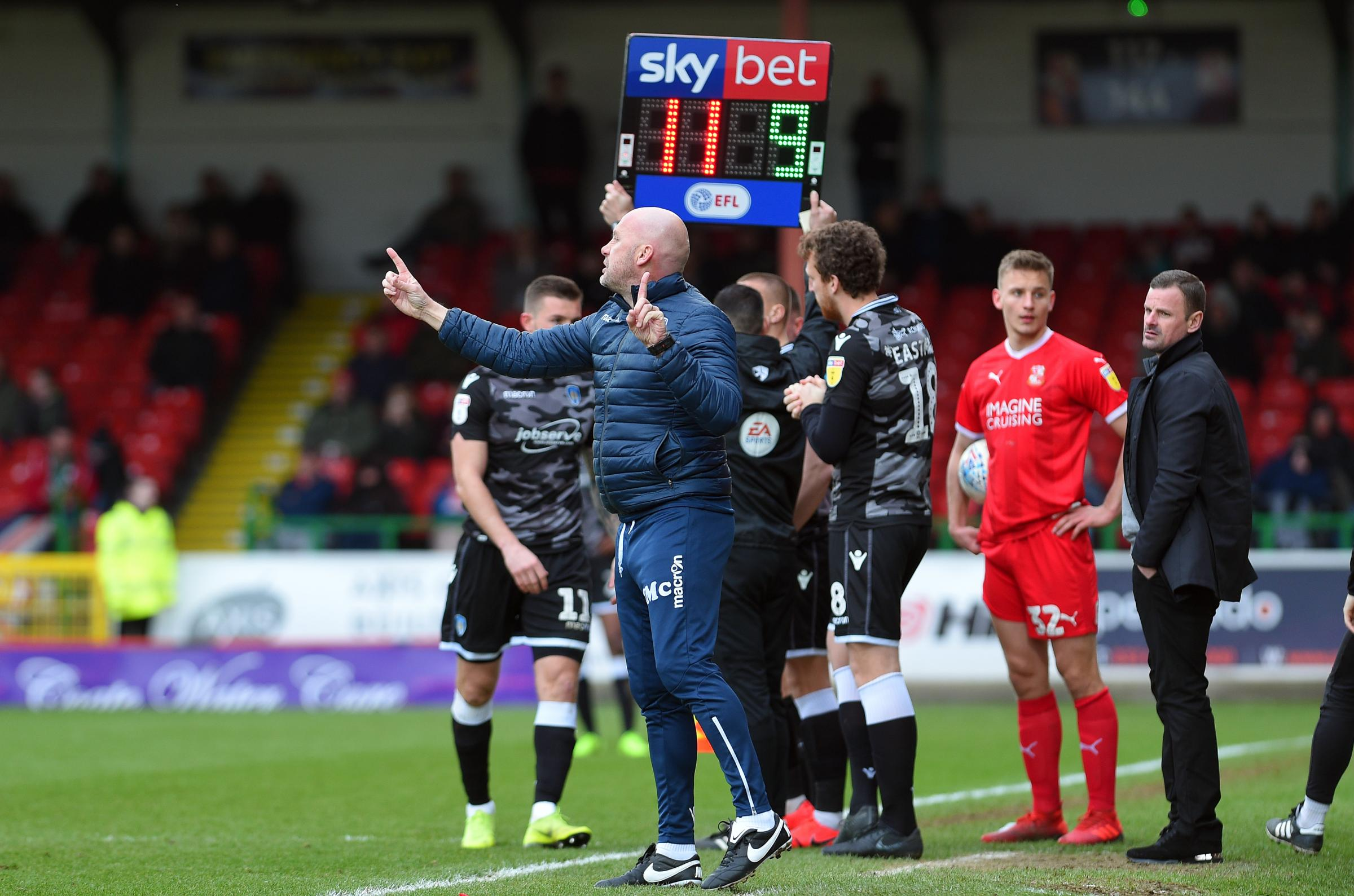 Watching brief - Swindon Town boss Richie Wellens (far right) watches on as his Colchester United counterpart John McGreal makes second-half changes Picture: PAGEPIX