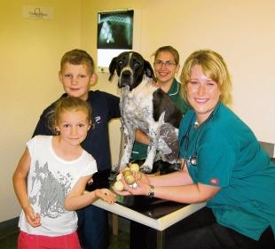Vet Emily Nightingale, right, with veterinary nurse Nikki Shaw, Bertie's owner's children Ben and Victoria, and Bertie, the golf balls and bullet