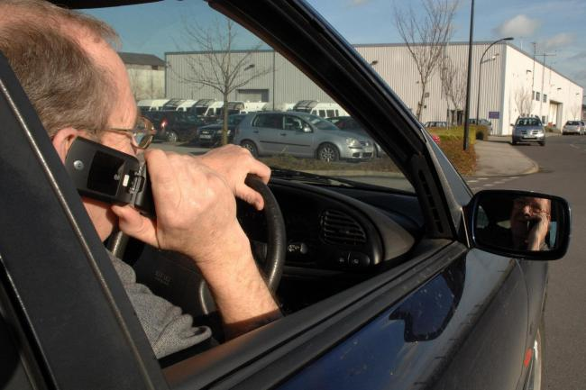 Picture posed by a model of a driver talking on his mobile phone while driving